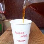 テイクアウトカップにコーヒーを注ぐ